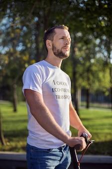 白いtシャツを着た男は、公園のぼやけた表面に乗っている間彼の電動スクーターの腕を保持しています。