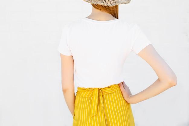 空白の白いtシャツと明るいオレンジ色のスカートの若い女性のクローズアップ