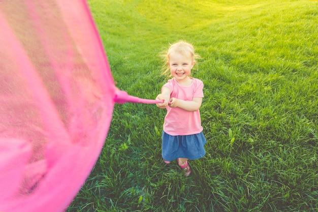 ピンクのtシャツとデニムのスカートを着た小さなかわいい女の子が野原を駆け回り、蝶を捕まえます。