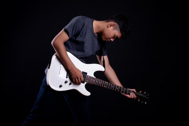 エレクトリックギターと暗いtシャツの若い男