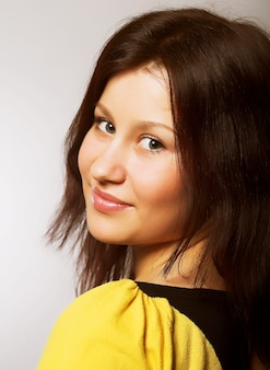 黄色のtシャツのブルネットの少女