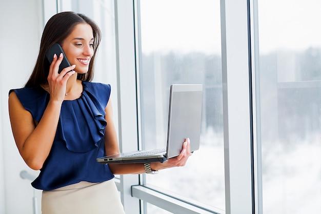 青いtシャツと黒いスカートに身を包んだビジネス女性は、コンピューターに取り組んでいます。