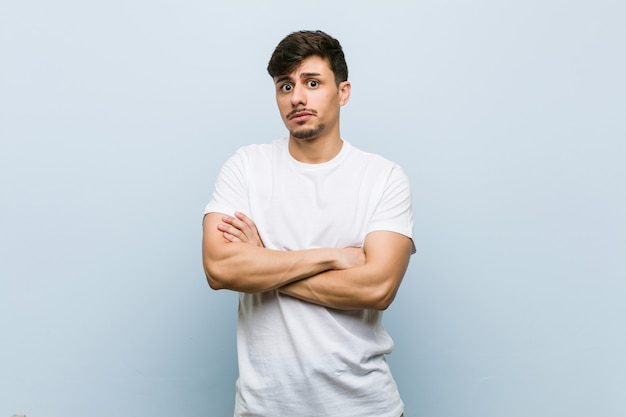 皮肉な表情で見ている不幸な白いtシャツを着ている若い白人男。