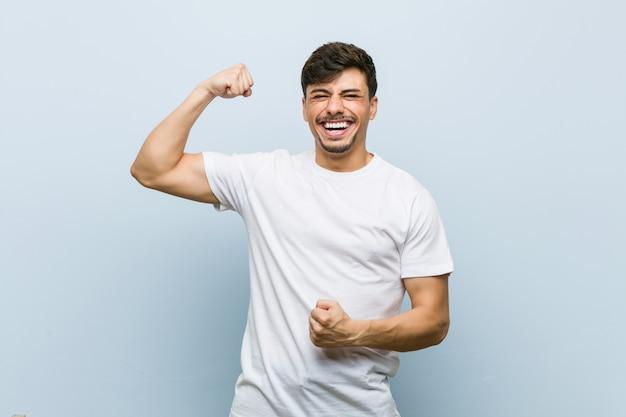 勝利、勝者の概念の後拳を上げる白いtシャツを着ている若い白人男。