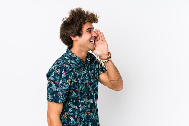 花のtシャツを着た若い白人男は叫び、開いた口の近くの手のひらを保持を分離しました。