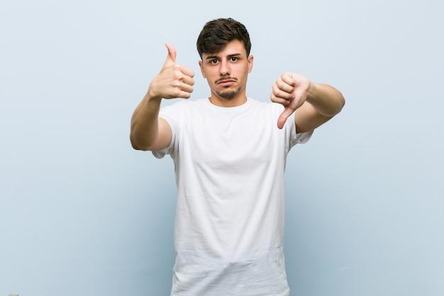 親指アップと親指ダウンを示す白いtシャツを着ている若い男