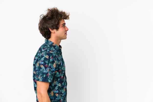 花のtシャツを着ている若い白人男は、注視左、横向きのポーズを分離しました。