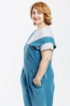 デニムのオーバーオールと白いtシャツに赤い髪の美しい中年女性の笑顔。活動と長寿。白い壁。垂直。