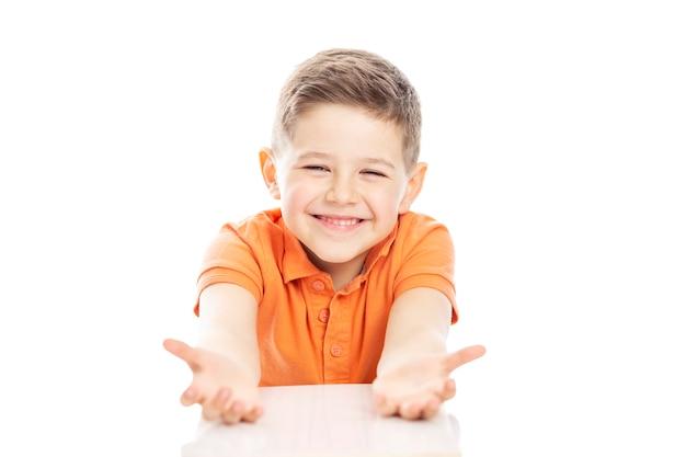 オレンジ色のtシャツを着たかわいい笑っている学齢期の少年がテーブルに座って、両手を広げています。白い背景に分離しました。