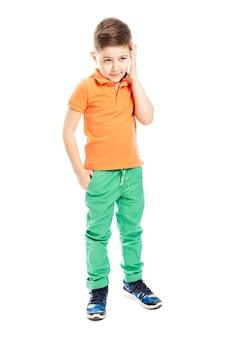 明るいオレンジ色のポロtシャツを着たかわいい学齢期の少年がスマートフォンで話しています。全高。垂直。白い背景に分離しました。