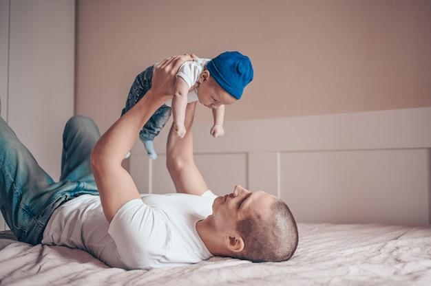 ブルージーンズと白いtシャツとキャップで赤ちゃんを抱いて幸せな若いお父さん父の肖像画を間近します。若い幸せな家族、寝室でかわいい感情的な小さな新生児の息子と遊ぶお父さん。