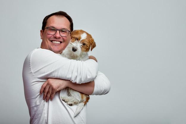 犬は飼い主の肩の上に横たわっています。白い背景の上の彼の所有者の手でジャックラッセルテリア。人と動物の概念。 t