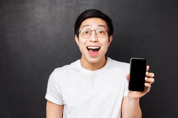 技術、メッセージング、人々の概念。クールなアプリに驚かされたスマートフォンのディスプレイを示す、白いtシャツを着た幸せ、驚き、感銘を受けた若い興奮しているアジア人のクローズアップの肖像画