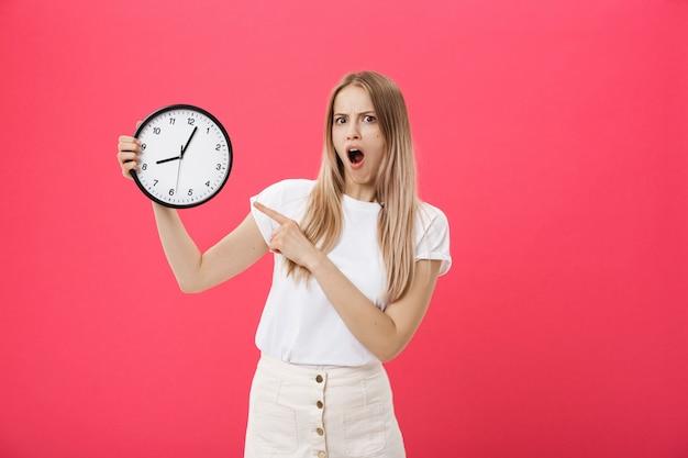 驚く女性持株時計。白いtシャツで驚いた女性は黒い時計を保持します。レトロなスタイル時間の節約の概念サマーセール。ディスカウント。ピンクの背景に分離されました。