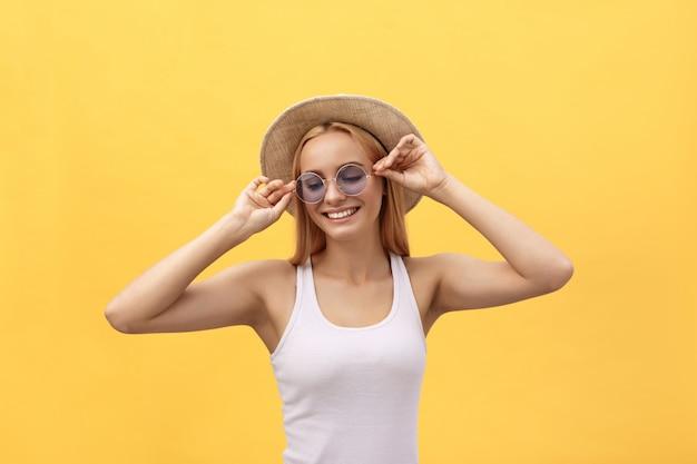 肯定的なニュースや誕生日の贈り物で歓喜の白いtシャツを着て幸せな陽気な若い女