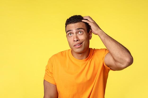 Tシャツの優柔不断な物思いにふけるハンサムな男は、頭をかいて混乱して見上げる