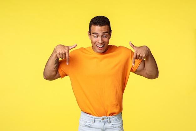 オレンジ色のtシャツで見栄えの良いハンサムな男