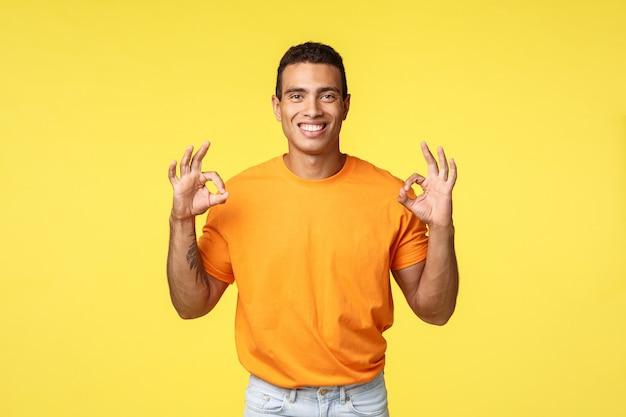 オレンジ色のtシャツ、白いズボン、入れ墨の腕を持つ魅力的な幸せな男は大丈夫ショー