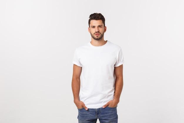 白で隔離される白いtシャツで笑顔の若い男の肖像画。