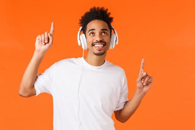 白いtシャツで幸せな笑みを浮かべてアフリカ系アメリカ人、見上げるとヘッドフォンを使用して音楽を聴くように笑顔、ジェスチャーの明るいビート、新しい曲、クールなプレイリスト、オレンジの壁を楽しむ