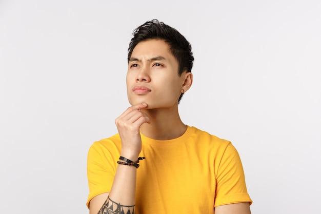 黄色のtシャツの思考でかわいいアジア男