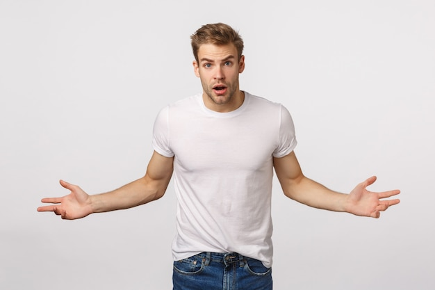 広がる手で白いtシャツで魅力的な金髪のひげを生やした男
