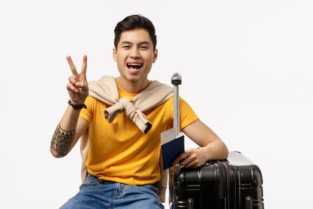 パスポートを保持している旅行の準備ができて黄色のtシャツでかわいいアジア男