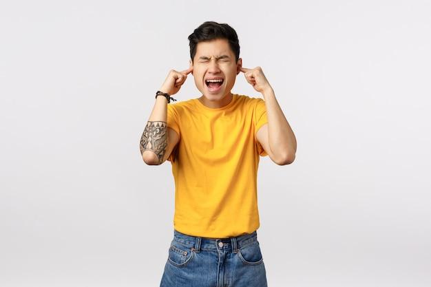 黄色のtシャツでかわいいアジア人は目と耳を指で閉じます