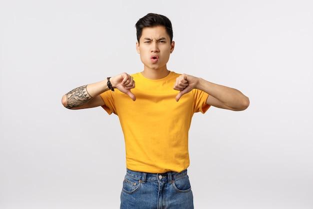 親指ダウンを示す黄色のtシャツでハンサムな若いアジア人