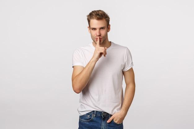 青い目と沈黙を求めて白いtシャツとハンサムな金髪の男