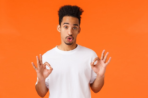 悪い映画ではないフィードフィードを与えるガイの評価。白いtシャツでかわいい流行に敏感な現代アフリカ系アメリカ人男性は、個人的な意見を表現し、大丈夫、良いジェスチャー、オレンジ色に立っています。