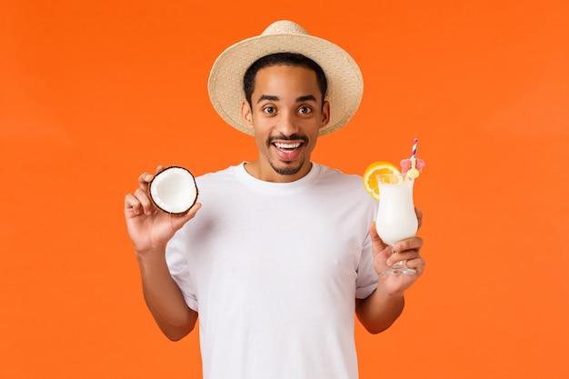 観光、休暇、レジャーのコンセプト。魅力的な低温とリラックスしたアフリカ系アメリカ人男性、白いtシャツ、夏の帽子、ココナッツとアルコール飲料を保持、カクテルを楽しんで旅行を飲む