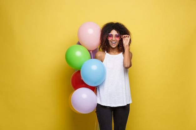 祝賀コンセプト - クローズアップ肖像画幸せな若い美しいアフリカの女性は、黒のtシャツでカラフルなパーティーバルーンで笑顔。イエローパステルスタジオの背景。
