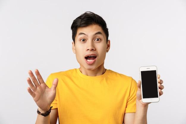 黄色のtシャツを着た魅惑的な完全に感銘を受けた若いアジア人男性、エキサイティングなニュースを伝え、信じられないほどのアプリケーションを示し、手を振ってオンラインアプリについて話し合って、電話を持ち、白い壁に立っている