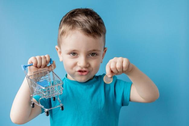青いtシャツの少年は、青色の背景にショッピングカートとコインを保持しています。ショッピングと販売のコンセプト。