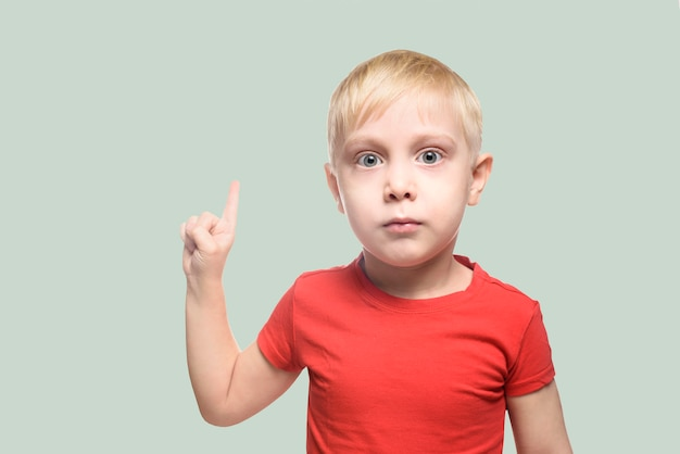 赤いtシャツで驚いた小さな金髪の少年は立ち、人差し指で上向きにポイントします。薄緑色の暗所で隔離