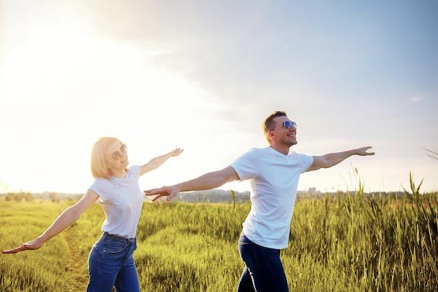白いtシャツ、サングラス、ジーンズで笑顔のカップルが飛行機を模した腕を広げる