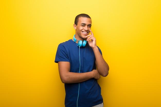 甘い表現を浮かべて黄色の背景に青いtシャツを持つアフリカ系アメリカ人の男