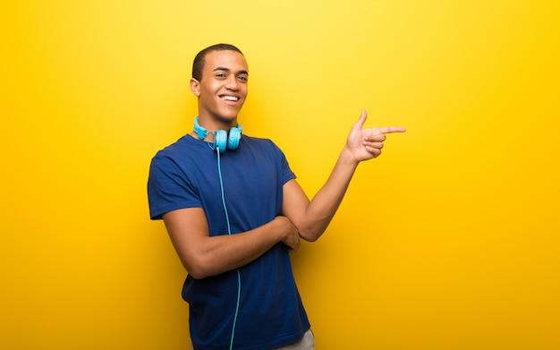 黄色の背景に指を指している青いtシャツを持つアフリカ系アメリカ人の男