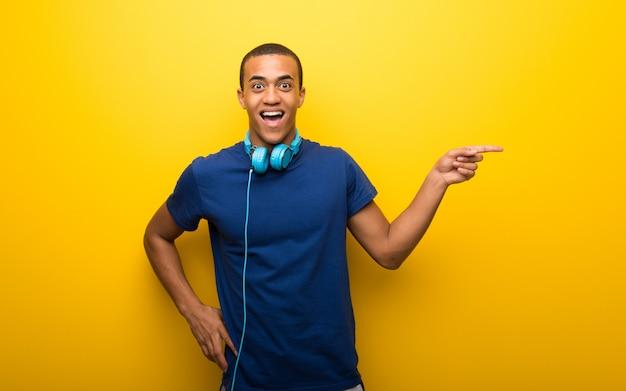青いtシャツを持つアフリカ系アメリカ人の男