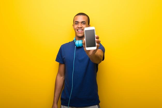 カメラを見て黄色の背景に青いtシャツを持つアフリカ系アメリカ人の男