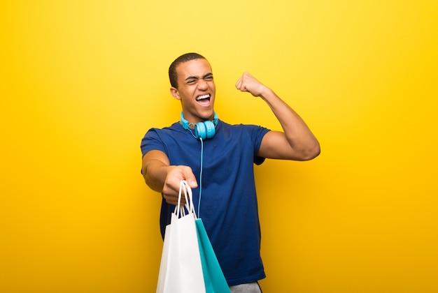 多くの買い物袋を保持している黄色の背景に青いtシャツを持つアフリカ系アメリカ人