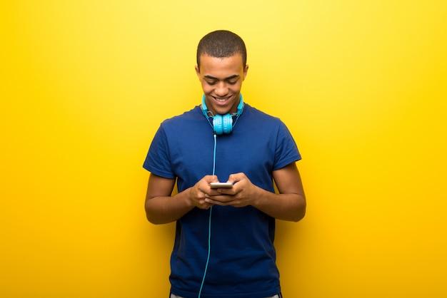 携帯電話でメッセージやメールを送信する黄色の壁に青いtシャツを持つアフリカ系アメリカ人