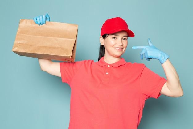 青い壁にボックスを保持しているピンクのtシャツの赤い帽子青い手袋の若い女性の宅配便