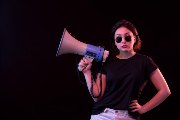メガホンを保持している黒のtシャツの若い女性