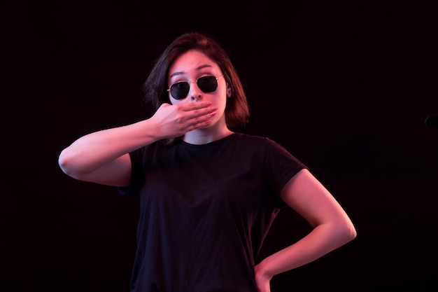 黒のtシャツとサングラスを持つ若い女性