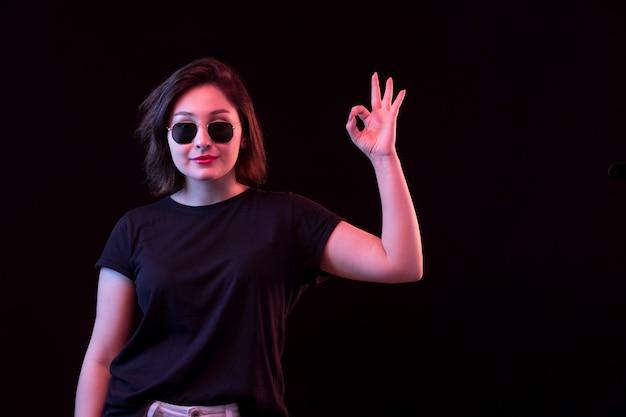 黒のtシャツを持つ若い女