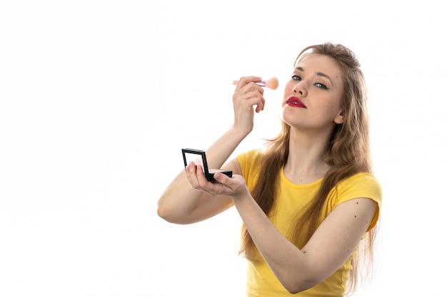 メイクアップを使用して黄色のtシャツを持つ若いブロンドの女性