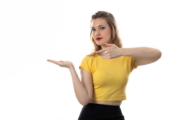 黄色のtシャツを持つ若いブロンドの女性