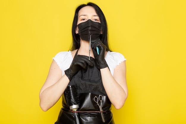 黒の滅菌マスク黒手袋ではさみを保持している白いtシャツ黒ケープの正面の若い女性美容師